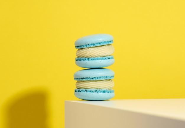 Macarons rotondi blu al forno su un fondo giallo, dessert delizioso