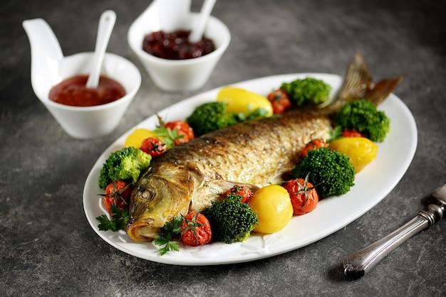 Carpa al forno con patate, pomodorini e broccoli