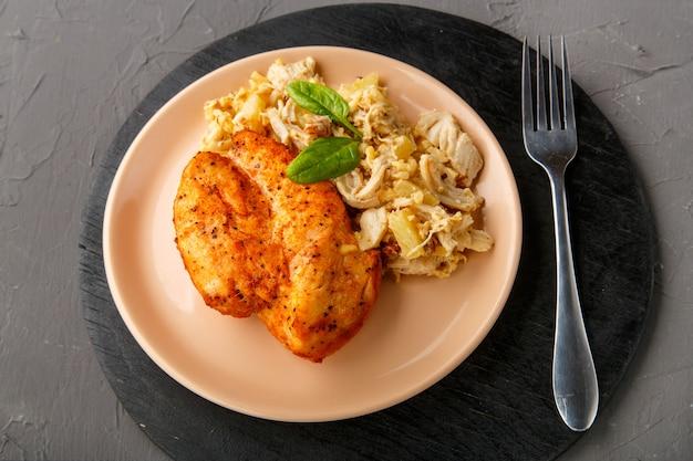 Petto di pollo al forno su un piatto beige con insalata di ananas su un tavolo su un supporto rotondo su uno sfondo concreto accanto a una forchetta. foto orizzontale