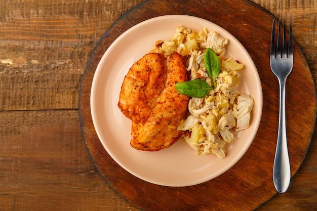 Petto di pollo al forno su un piatto beige con insalata di ananas su un tavolo su un supporto rotondo accanto a una forchetta. foto orizzontale