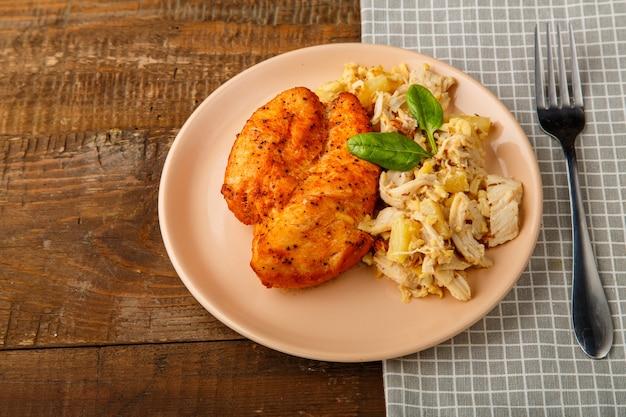 Petto di pollo al forno su un piatto beige con insalata di ananas su un tavolo su un supporto rotondo. foto orizzontale