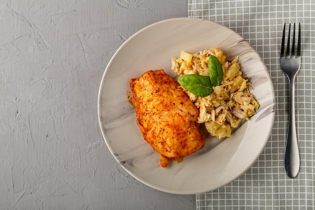 Petto di pollo al forno su un piatto grigio con insalata di ananas su un tavolo su un tovagliolo su uno sfondo di cemento vicino a una forchetta. foto orizzontale