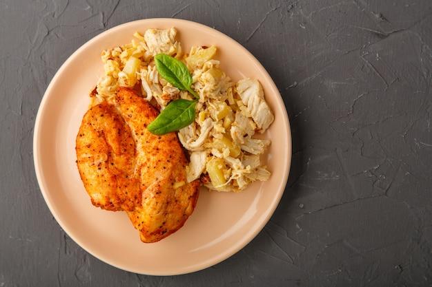 Petto di pollo al forno su un piatto con insalata di ananas su un tavolo su uno sfondo concreto. foto orizzontale