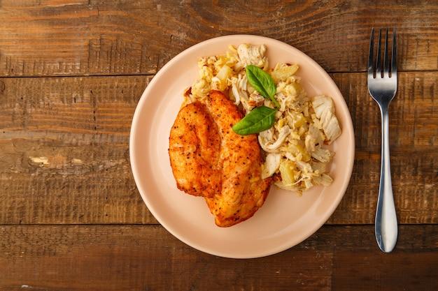 Petto di pollo al forno in salsa con insalata su un piatto accanto a una forchetta su un tavolo di legno