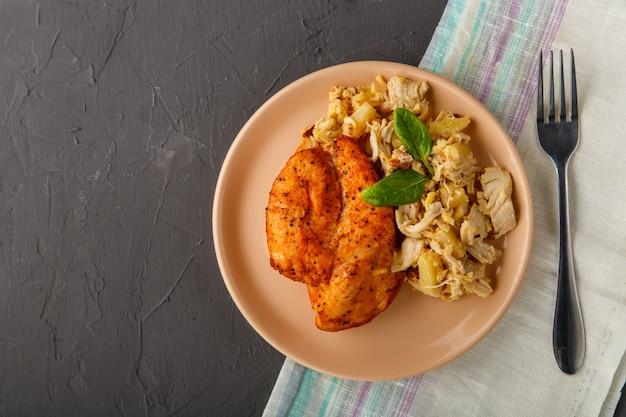 Petto di pollo al forno con insalata su un piatto decorato con spinaci accanto a una forchetta su un fondo concreto