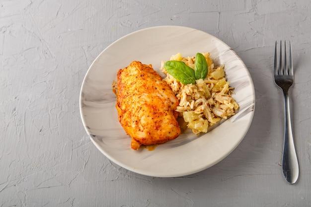 Petto di pollo al forno con insalata su un piatto accanto a una forchetta su uno sfondo grigio foto orizzontale