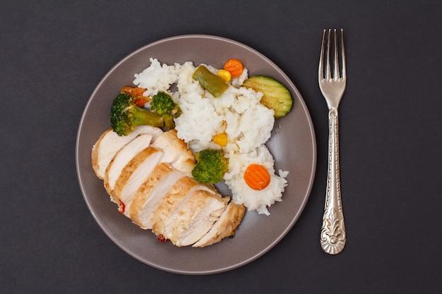 Petti di pollo al forno o filetto con riso, verdure e verdure su un piatto con forchetta. sfondo nero. vista dall'alto.