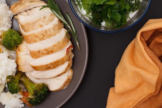Petti di pollo al forno o filetto con riso, verdure e verdure su piatto con ciotola di vetro con salsa. vista dall'alto.