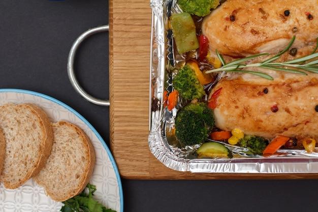 Petti di pollo al forno o filetto con verdure e verdure in contenitore di metallo, piatto con pane su un tagliere di legno, vista dall'alto.