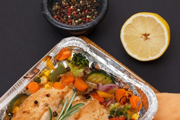 Petti di pollo al forno o filetto con verdure e verdure in un contenitore di metallo su un tagliere di legno. ciotola in vetro con peperoni pimento e limone. vista dall'alto.