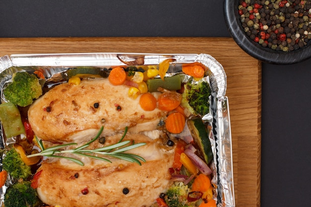 Petti di pollo al forno o filetto con verdure e verdure in un contenitore di metallo su un tagliere di legno. ciotola di vetro con peperoni pimento. vista dall'alto.