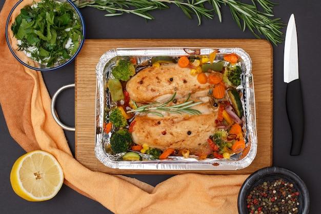 Petti di pollo al forno o filetto con verdure e verdure in un contenitore di metallo su un tagliere di legno. ciotola di vetro con salsa, limone, pepe di pimento e coltello. vista dall'alto.