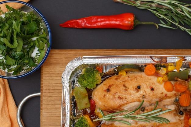 Petti di pollo al forno o filetto con verdure e verdure in un contenitore di metallo su un tagliere di legno. ciotola di vetro con salsa, peperoncino e spezie. vista dall'alto.