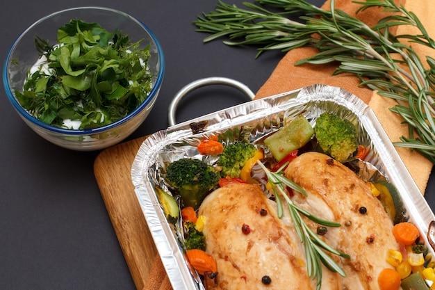 Petti di pollo al forno o filetto con verdure e verdure in un contenitore di metallo su un tagliere di legno. ciotola di vetro con salsa e rosmarino. vista dall'alto.