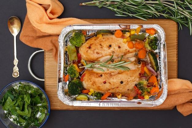 Petti di pollo al forno o filetto con verdure e verdure in un contenitore di metallo su un tagliere di legno. ciotola di vetro con salsa, cucchiaio e rosmarino. vista dall'alto.