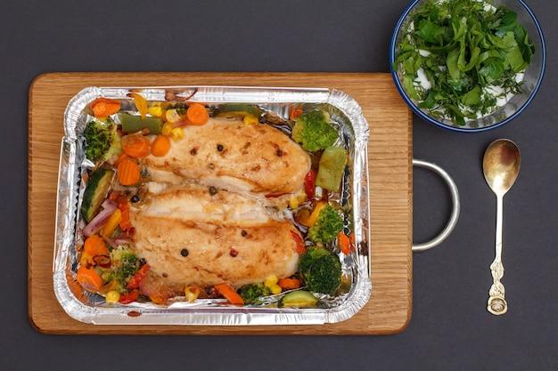Petti di pollo al forno o filetto con verdure e verdure in un contenitore di metallo su un tagliere di legno. ciotola di vetro con salsa e cucchiaio. vista dall'alto.