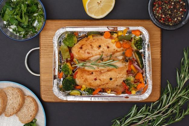 Petti di pollo al forno o filetto con verdure e verdure in un contenitore di metallo su un tagliere di legno. ciotole in vetro con salsa e peperoni pimento, limone, piatto con pane. vista dall'alto.