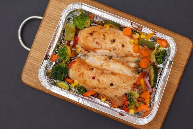 Petti di pollo al forno o filetto con verdure e verdure in contenitore di metallo su tagliere di legno. vista dall'alto.