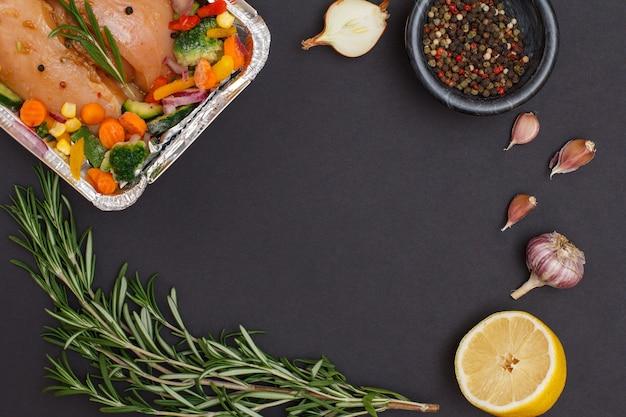 Petti di pollo al forno, aglio, cipolla, limone, peperoni in una ciotola e rosmarino su sfondo nero. vista dall'alto.