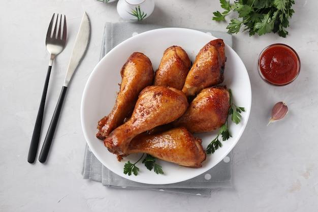 Cosce di pollo al forno in salsa di soia e miele su piatto bianco su sfondo chiaro. avvicinamento. vista dall'alto