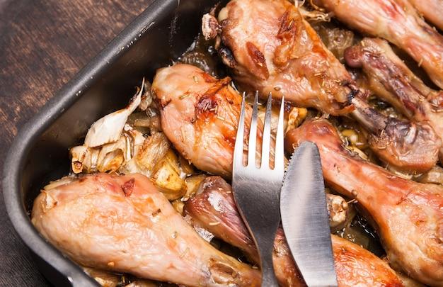 Coscie di pollo al forno in vassoio su di legno nero