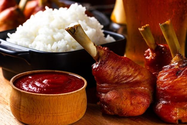 Cosce di pollo al forno con un bicchiere di birra e cena con ketchup al pub in