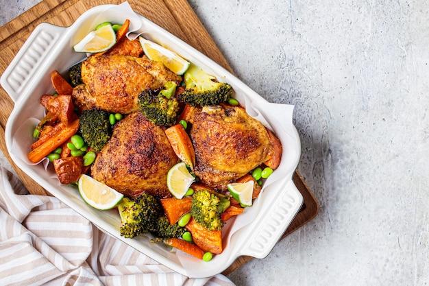 Pollo al forno con verdure, sfondo grigio, vista dall'alto, copia dello spazio.