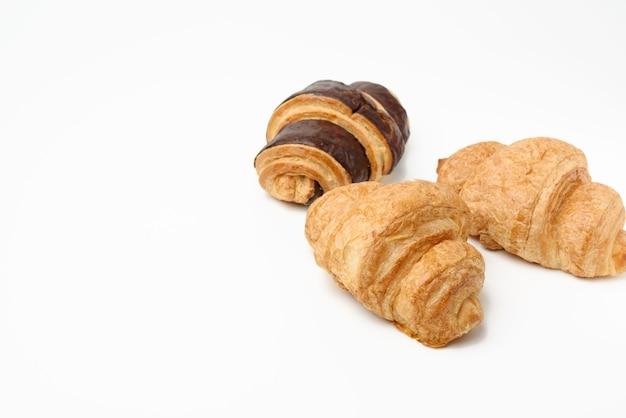 Croissant al cioccolato al forno a base di farina di frumento bianco su sfondo bianco, copia dello spazio