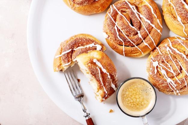 Panini alla cannella al forno serviti con cannella e caffè su sfondo bianco trama. vista dall'alto, piatto. copia spazio