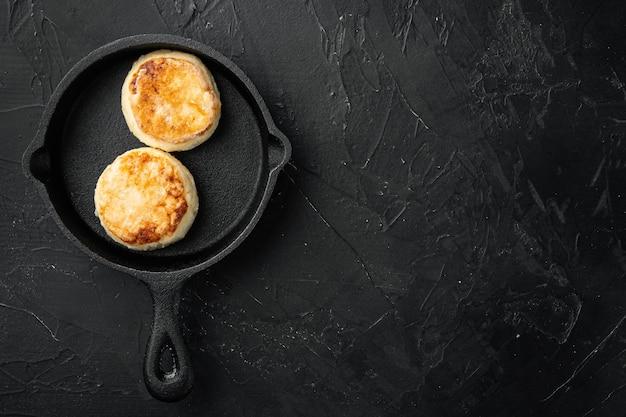 Frittelle di ricotta al forno su ghisa padella padella su ghisa padella padella, vista dall'alto piatta, su tavola di pietra scura nera