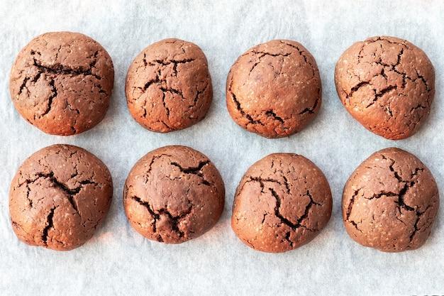 Biscotti al cioccolato rotondi incrinati al forno su una teglia