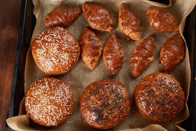 Croissant al forno e panini rotondi con semi di sesamo su una teglia di ferro con carta da forno marrone arrotolata