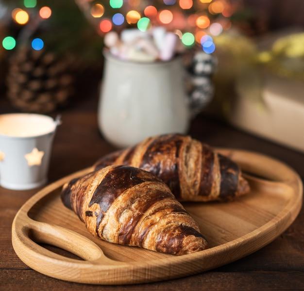 Croissant al forno e una tazza di ceramica bianca con caffè, dietro le luci di natale accese, da vicino