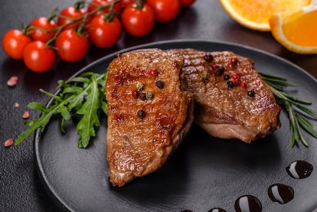 Petto d'anatra al forno con erbe e spezie su una superficie di cemento scuro. carne fritta pronta da mangiare