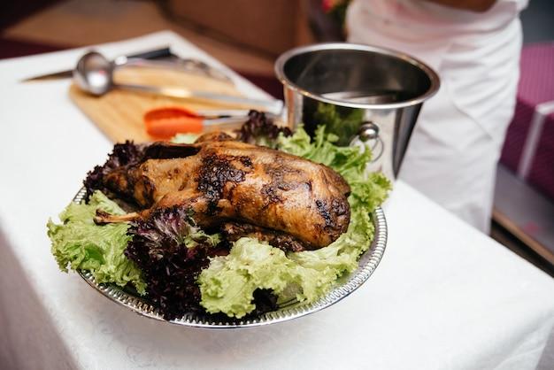 Anatra al forno su un piatto con verdure e insalata