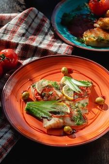 Pesce al forno in un piatto di argilla arancione con limone e olive al buffet