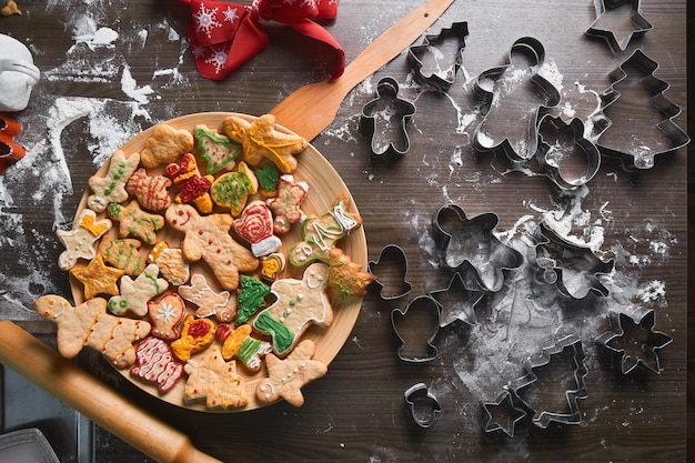 Omino di pan di zenzero al forno, biscotti di diverse forme giacciono su un vassoio di legno. il concetto delle tradizioni di capodanno e il processo di cottura. biscotti su una tavola di legno marrone. produzione familiare. panificio domestico