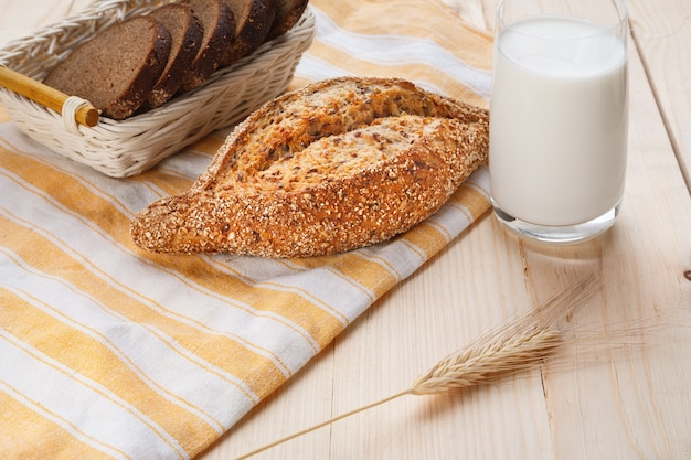 Pane di grano al forno con semi di lino con un bicchiere di latte sulla tavola di legno. concetto di cibo per la colazione. vista ravvicinata
