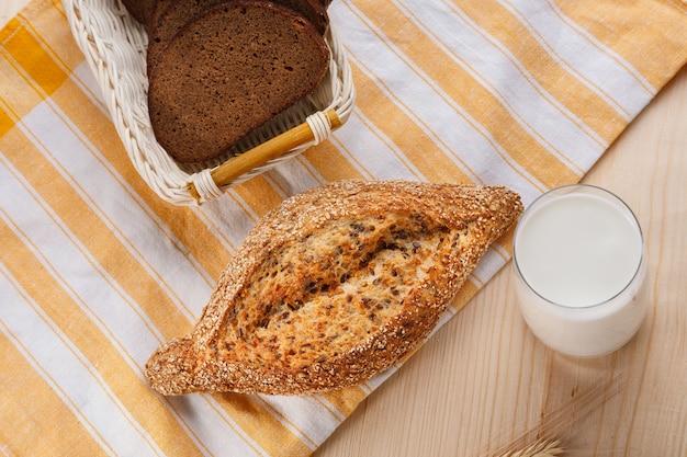 Pane di grano al forno con semi di lino con un bicchiere di latte sulla tavola di legno. concetto di cibo per la colazione. vista dall'alto