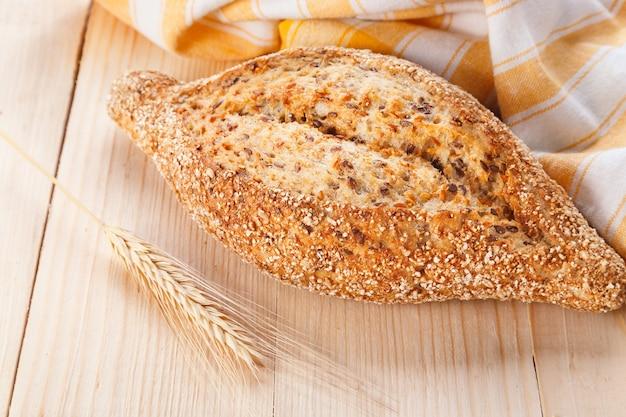 Pane di grano al forno con semi di lino sulla tavola di legno. vista ravvicinata