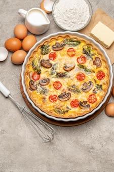 Torta di quiche fatta in casa al forno in forma di cottura in ceramica, uova e panna