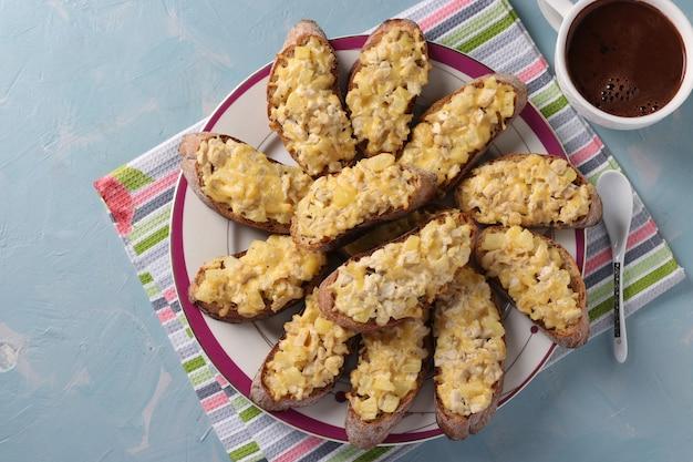 Toast fatti in casa al forno con pollo, formaggio, ananas e aglio e tazza di caffè su sfondo azzurro. vista dall'alto. avvicinamento