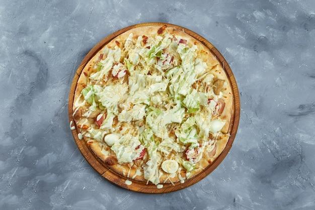 Pizza italiana al forno con pomodorini, lattuga, parmigiano, crostini di pane, pollo su un vassoio di legno su uno sfondo grigio. pizza cesare