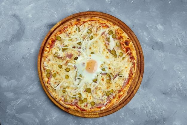 Pizza italiana al forno con pollo. cipolla, cetrioli sottaceto, salame e pomodori su un vassoio di legno su uno sfondo grigio.