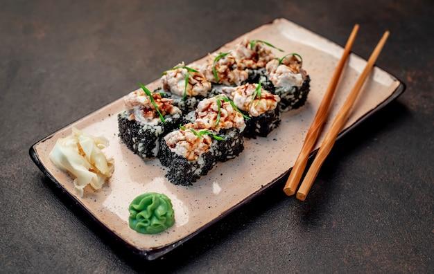 Rotoli di sushi giapponese al forno su uno sfondo di pietra