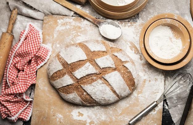 Pagnotta di pane al forno sul tavolo e ingredienti, utensili da cucina si trovano nelle vicinanze, vista dall'alto