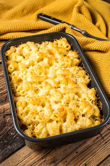 Mac e formaggio al forno piatto americano con salsa cheddar. fondo in legno. vista dall'alto.