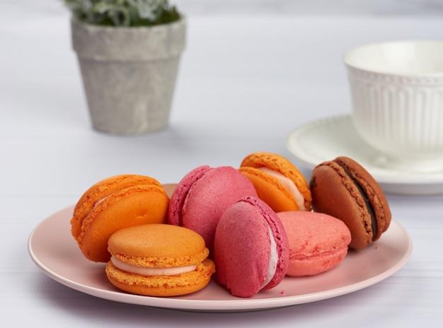 Macarons al forno su un piatto rosa, dietro una tazza bianca in ceramica con caffè, mattina