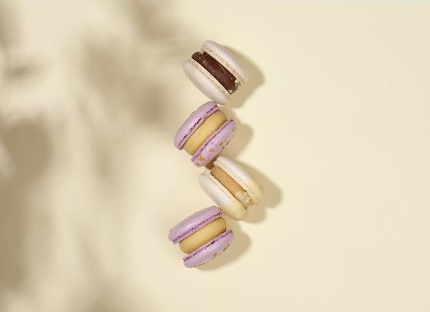 Macarons al forno con gusti diversi su fondo beige, vista dall'alto