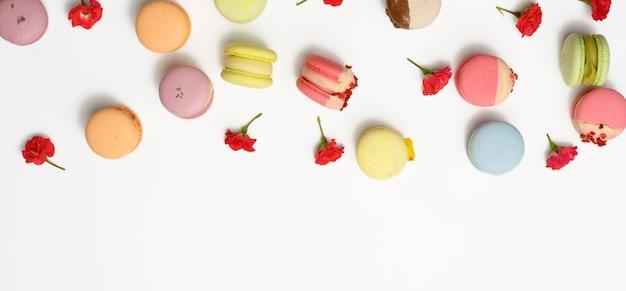Macarons al forno con diversi sapori e boccioli di rosa su sfondo bianco, vista dall'alto